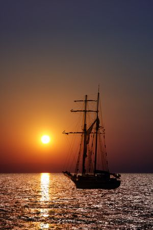 Sailing ship in sunrise. Vertical composition. photo