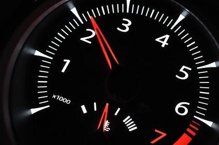 Part of cars dashboard. Illuminated tachometer closeup. Black background. photo