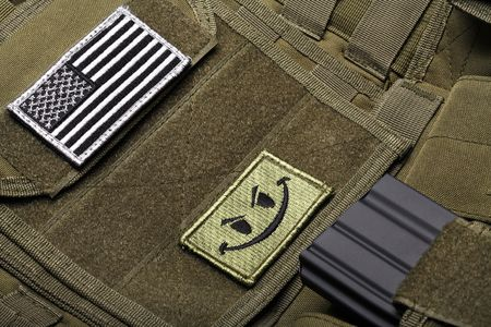 drab: American flag on a green (olive drab) tactical vest close-up.