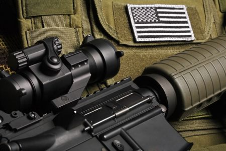 Military still life. Tactical vest with U.S. battle flag and assault rifle close-up.