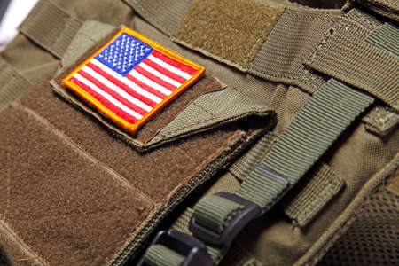 striped vest: American flag on a green (olive drab) tactical vest. Close-up. Stock Photo