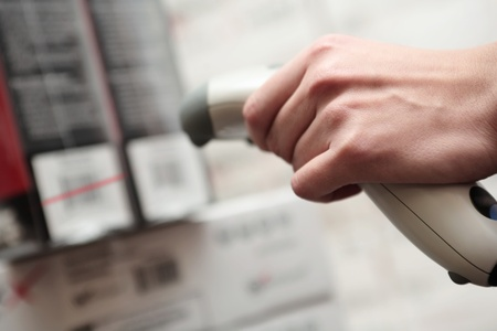 scanning: A man gets on the hip scaner in operations directed on printed barcode. Store scene. Shallow DOF. Stock Photo
