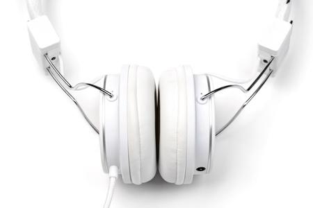 aural: White elegance headphones on white background close-up. White on white series.