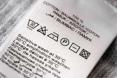 Clothing labels with laundry care symbols closu-up. Shallow DOF.