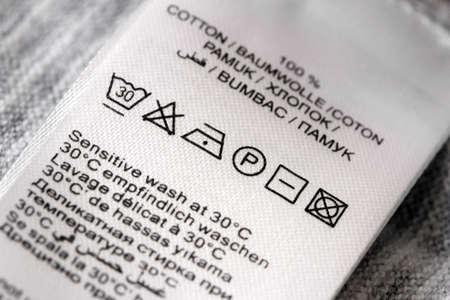 Laundry: Etiquetas de ropa con s�mbolos cuidado de la ropa closu-up. DOF Superficial.