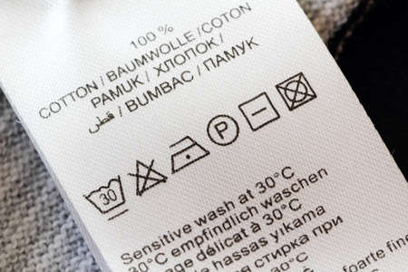 description: Clothing labels with laundry care symbols closu-up.