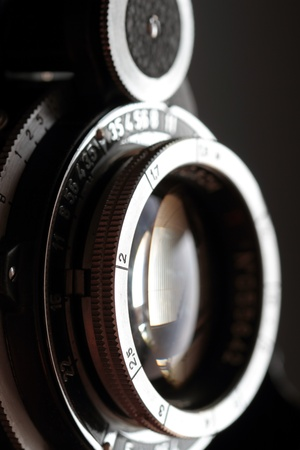 'retro styled': An old camera lens close-up on a dark background  Vertical composition  Stock Photo