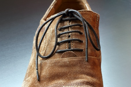 menswear: Part of brown mens suede shoe close-up  Grey background  Stock Photo