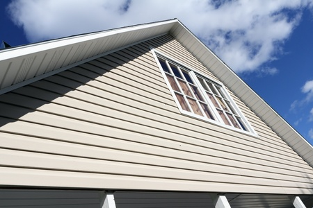 house siding: House exterior, against a blue sky. Roof close-up. Low angle view. Stock Photo