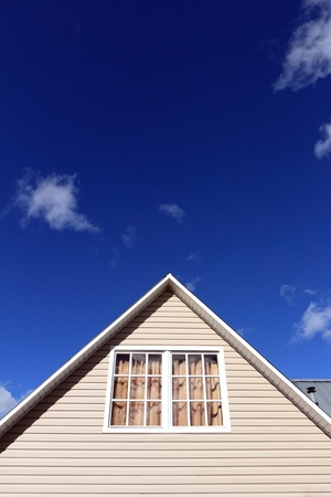 house siding: House roof against a blue sky. Vertical composition.