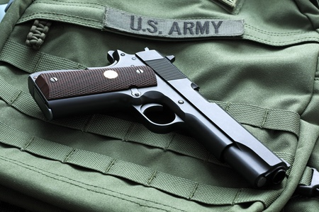 45 caliber: Legendary semi-automatic M1911 Mark IV Series 80 .45 caliber pistol on a green background with the U.S. Army patch. Studio shot.