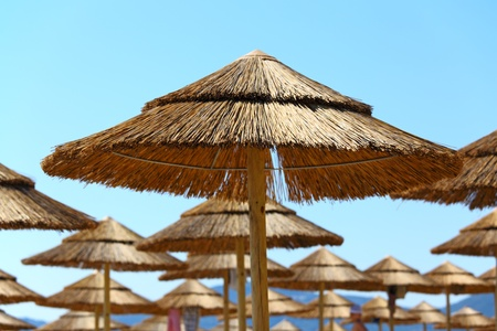 corfu: Straw umbrellas on the beach. Corfu Island, Greece