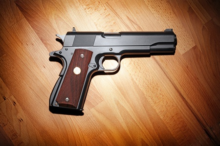 45 caliber: Semi-automatic M1911 Mark IV Series 80 .45 caliber pistol on the wooden table.