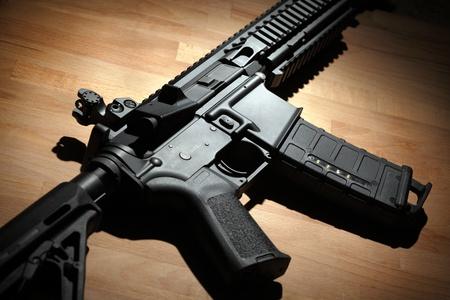 carbine: Modern custom AR-15 (M4A1) carbine on a wooden surface. Studio shot Stock Photo