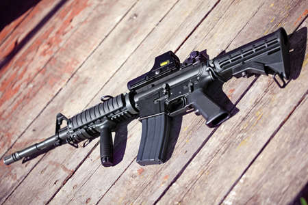 carbine: The Black Rifle. AR-15 assault carbine (M4A1) on a wooden surface. Shallow DOF.