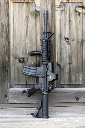 vertical composition: The Black Rifle. 14,5 AR-15 assault carbine (M4A1) with holographic sight against an old wooden door. Vertical composition.