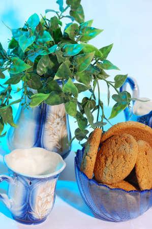 Porcelain tea set and biscuit in blue light  photo