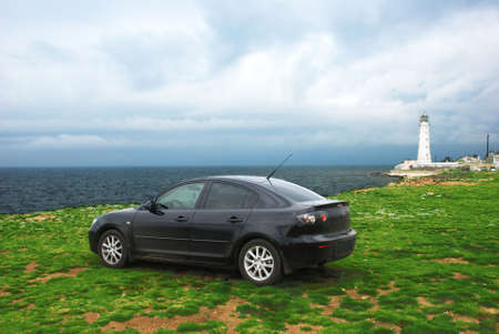 Modern car over lighthouse and sea storm Stock Photo - 4820347