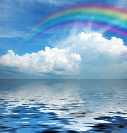 witte pluizige wolken in de blauwe lucht met rainbow  Stockfoto