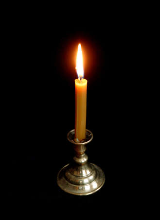 On a dark background a burning candle. photo