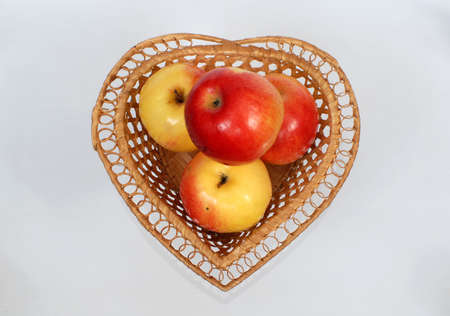 In an original vase in the form of heart ripe juicy apples lay. photo