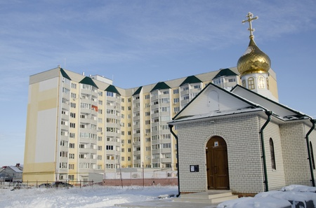 gold en: The Chapel with gold en  dome on background new building in village Jubilee in city Saratov  Editorial