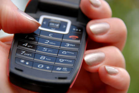 Womans hand holding mobile phone keypad photo