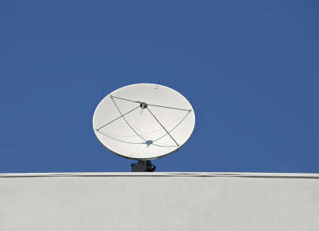 Satellite dish on roof, blue sky background photo