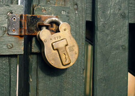 entry numbers: vintage brassy padlock on the green wooden fence