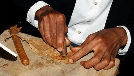 cheroot: close up of tobacconists  hands  on the wood plank Stock Photo