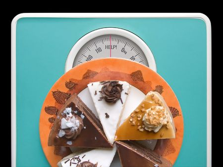 starvation: Chocolate cake on weigh-scale - help! Stock Photo
