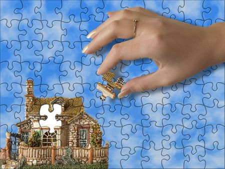 Build the house - hand bring piece of house (puzzle) photo