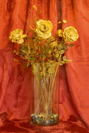 Golden roses in glass bowl, red background photo