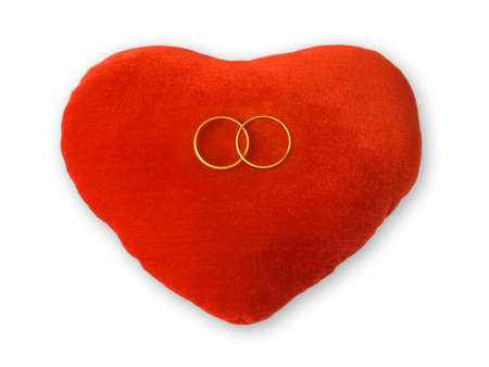 Golden rings on red heart, isolated on white photo