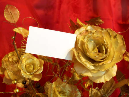 Golden roses and postcard on red background photo
