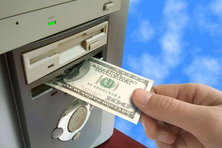 Hand put money to computer (internet business) Stock Photo