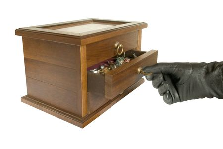 Hand in black glove opening casket with jewelry, isolated photo