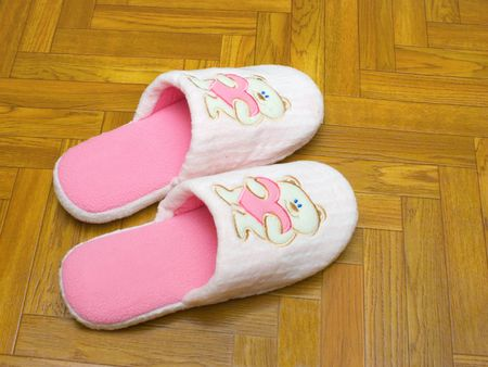 furskin: Childlike slippers on parquet, bear with  Stock Photo