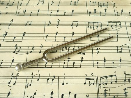 tunes: Fork on old sheet music, closeup