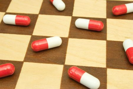 Pills on chessboard, close-up photo