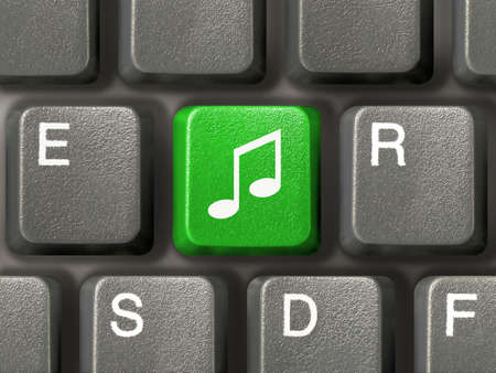Computer keyboard (close-up) with green music key photo