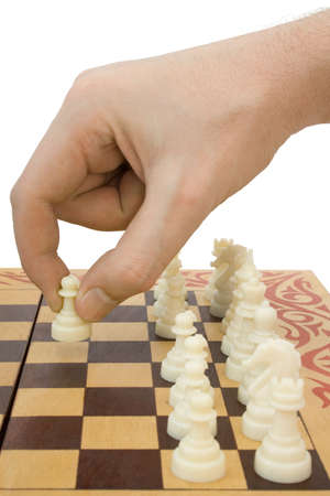 Pawn in hand and chessboard, isolated on white background photo