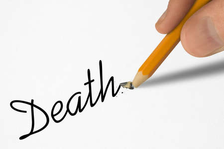 Word Death on paper and broken pencil in hand, close-up photo
