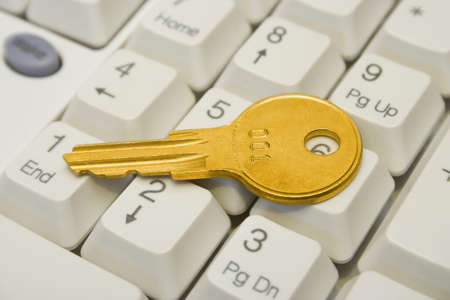 Golden key on computer keyboard, close-up photo