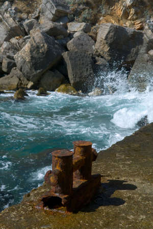 Old pier with a rusty bollard, surf on background photo