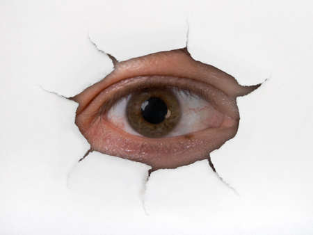 Eye looking through hole on paper surface Stock Photo - 1922671