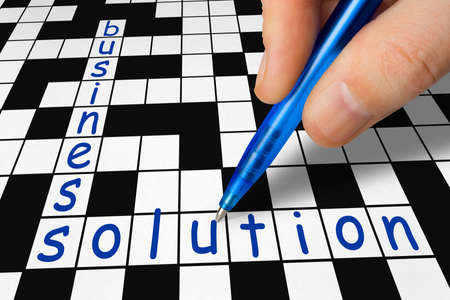 filling in: Hand filling in crossword - business and solution