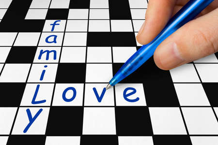 filling in: Hand filling in a crossword -  and love Stock Photo
