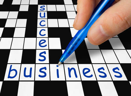 filling in: Hand filling in crossword - business and success