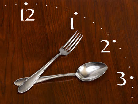 Clock made of spoon and fork on wooden table photo